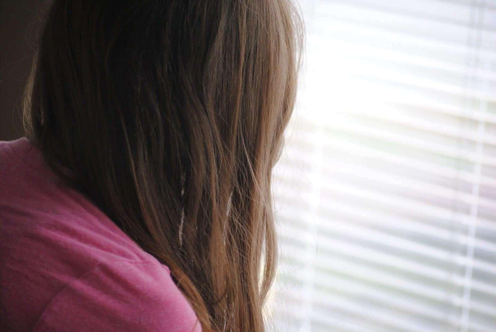 Frau leidet und schaut aus Fenster